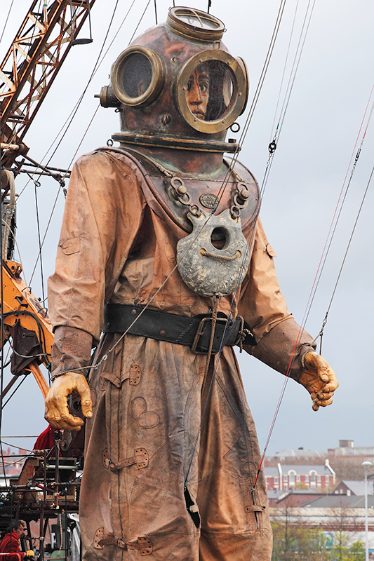 Giant Uncle rises from the water of Liverpool Docks dressed as a diver