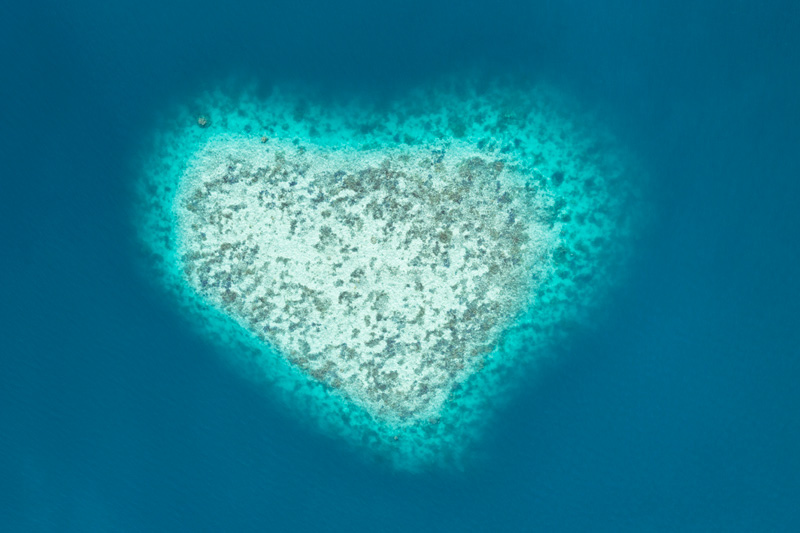 Heart shaped island in blue sea from above