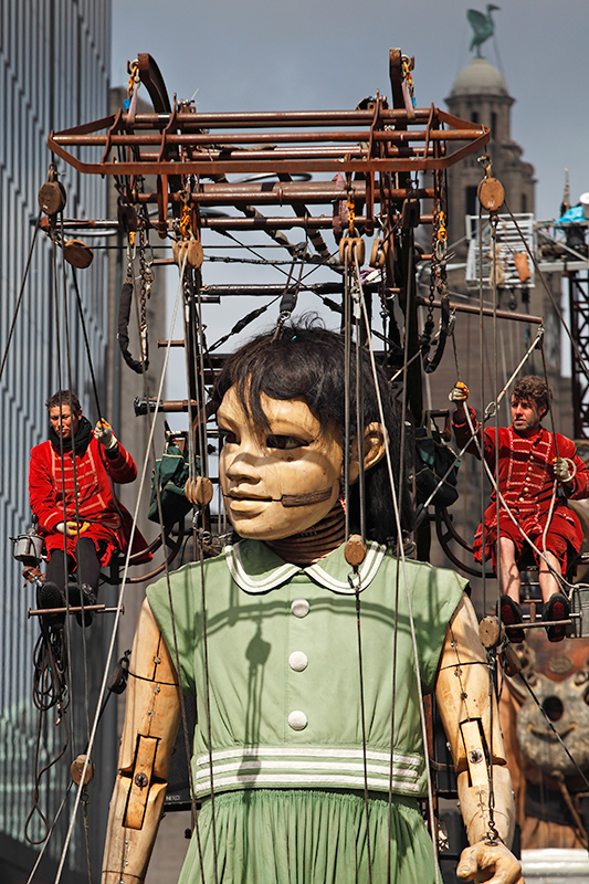 Little Girl Giant and Lilliputian puppeteers