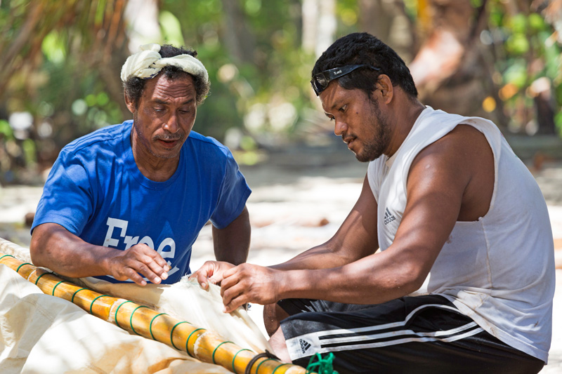 Yapese men working on a canoe sail